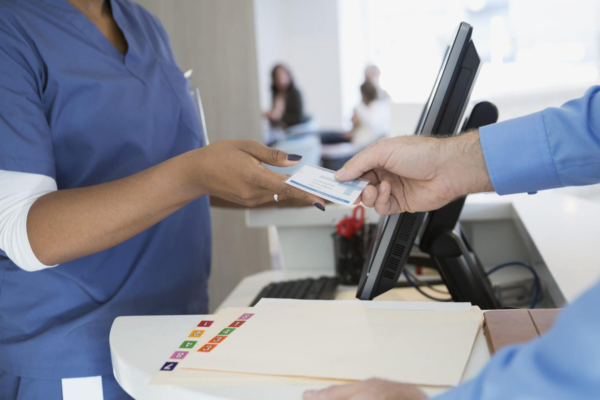 Person-handing-nurse-insurance-card-.jpg
