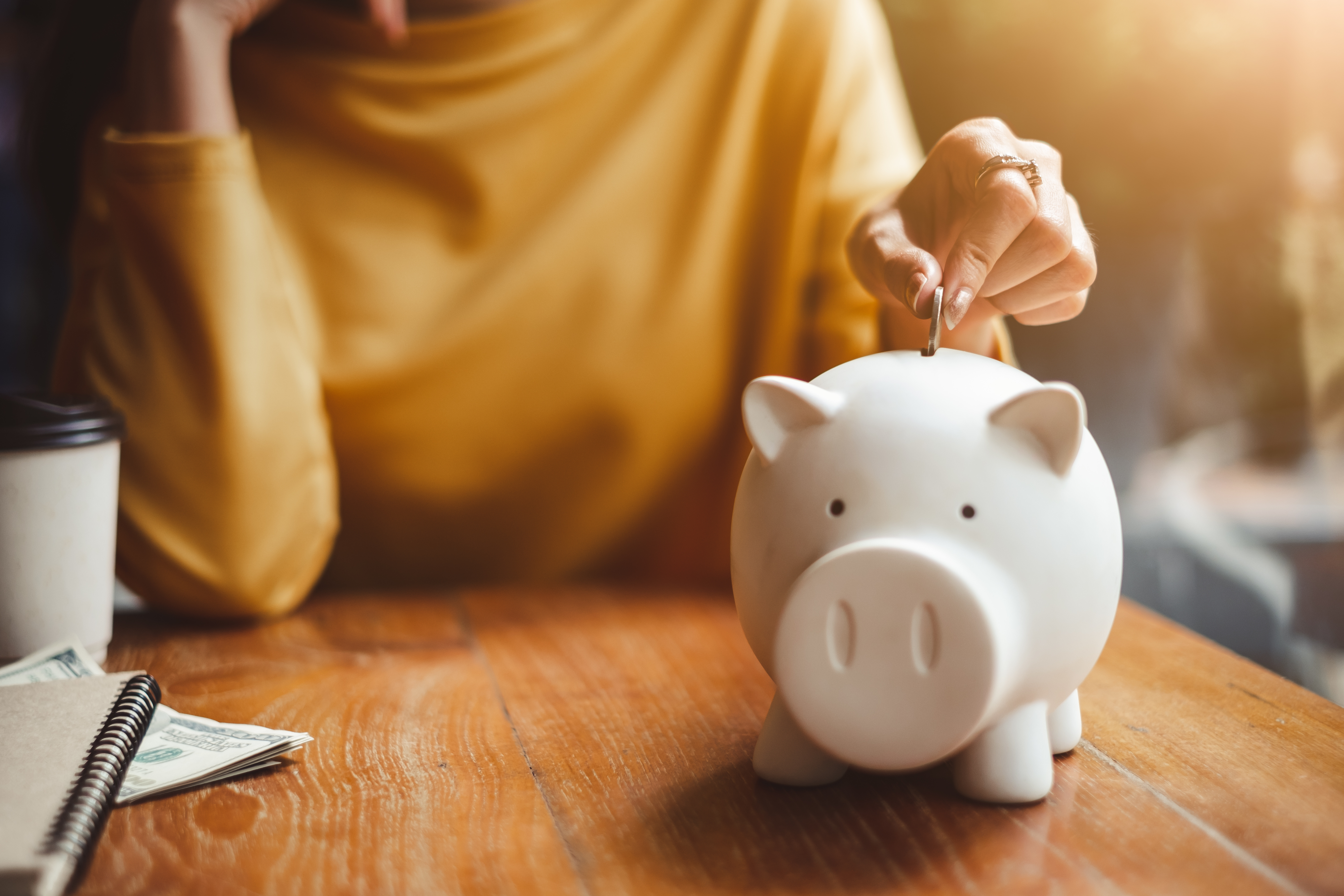 Woman-Putting-change-in-piggy-bank.-jpeg
