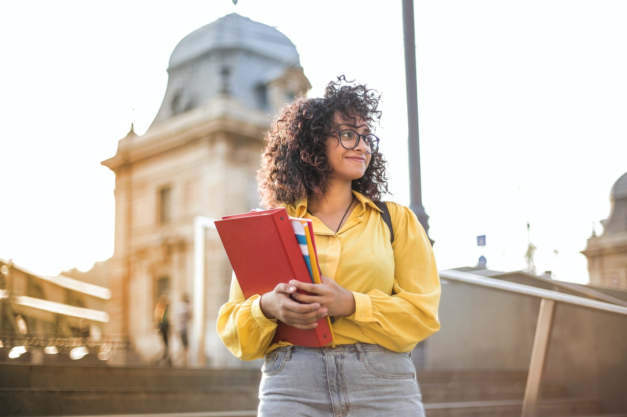 woman-in-yellow-jacket-holding-red-book.jpg